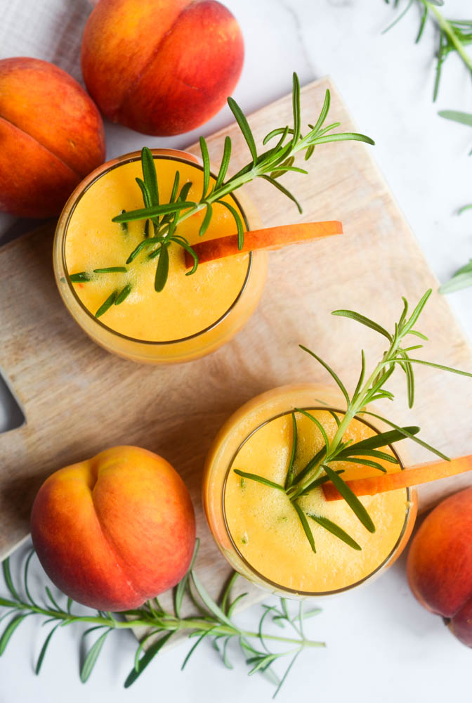 aerial picture of two peach bourbon cocktails on a wooden cutting board with a slice of peach over the rim and a sprig of rosemary in the drink.