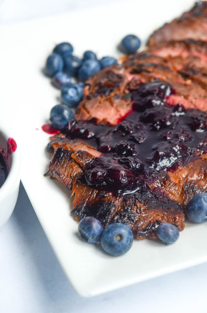 up close picture of sliced flank steak with blueberry sauce