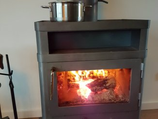 Houtkachel met pannetje soep erop tijdens kerstetentje
