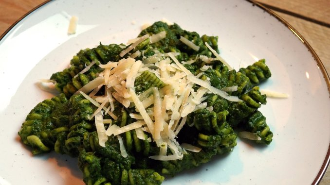 Pasta met palmkoolsaus en geraspte Pecorino kaas op bord