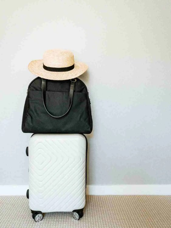 Carry-on bag stacked on suitcase with women's hat ready for minimalist travel