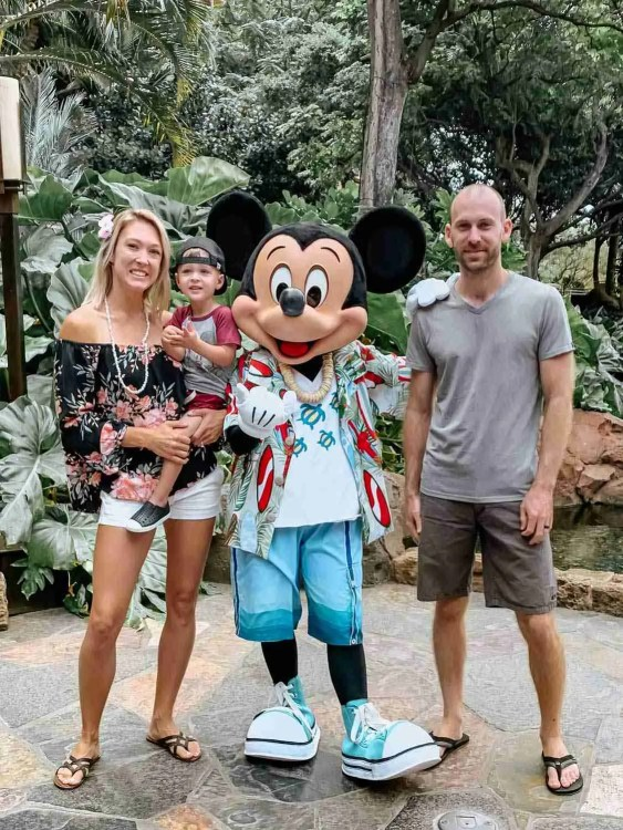 Family smiling with Mickey Mouse at Aulani with lush tropical trees surround in Hawaii