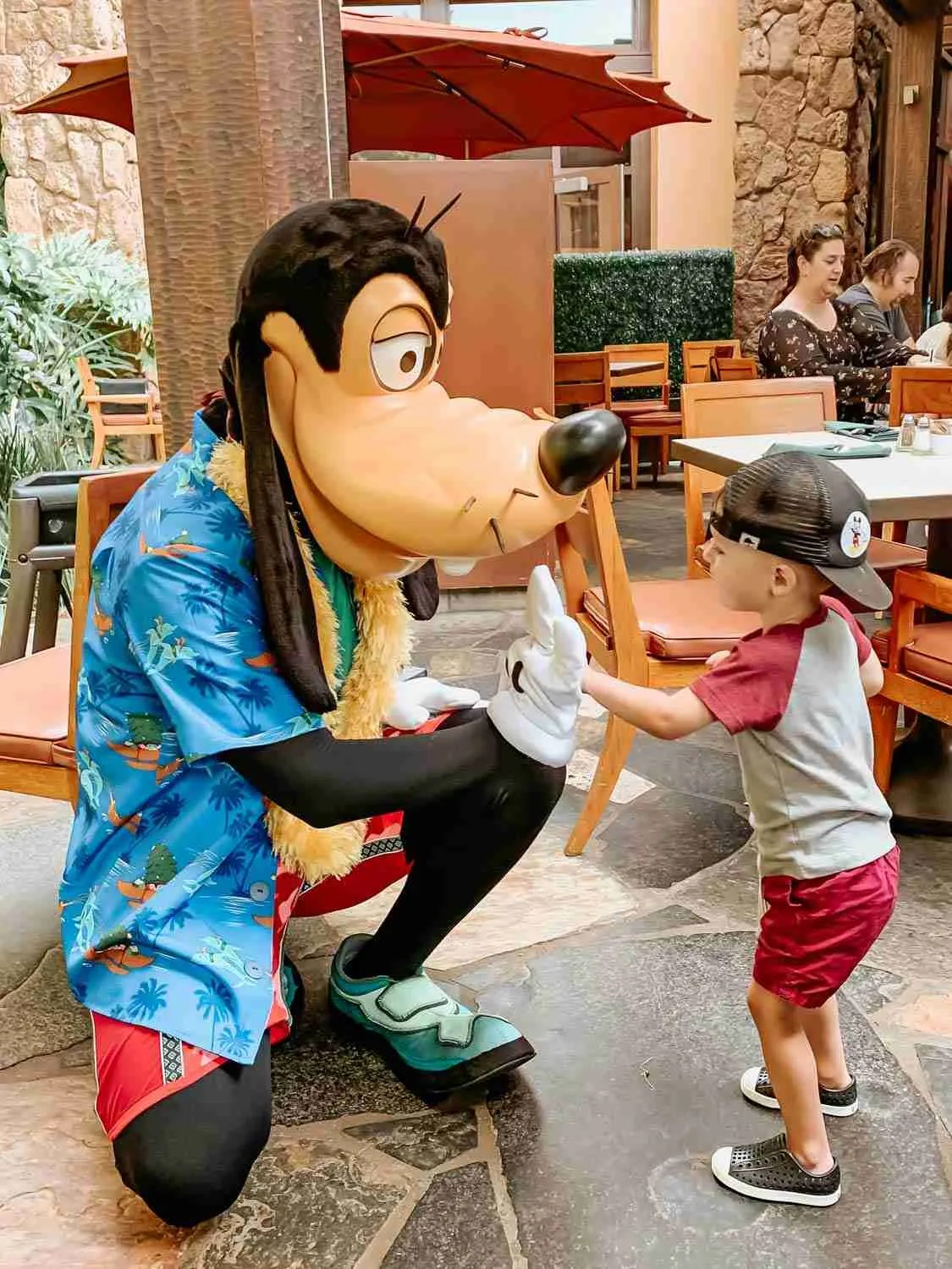Little boy giving Goofy a high five at the Disney Character Breakfast at Aulani