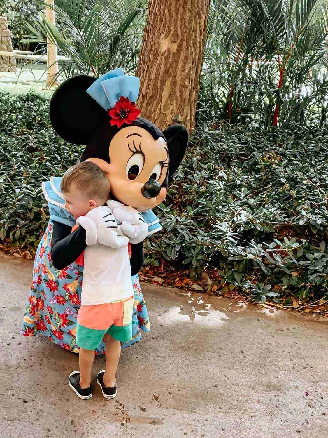 Little boy giving Minnie Mouse a hug at Aulani in Hawaii