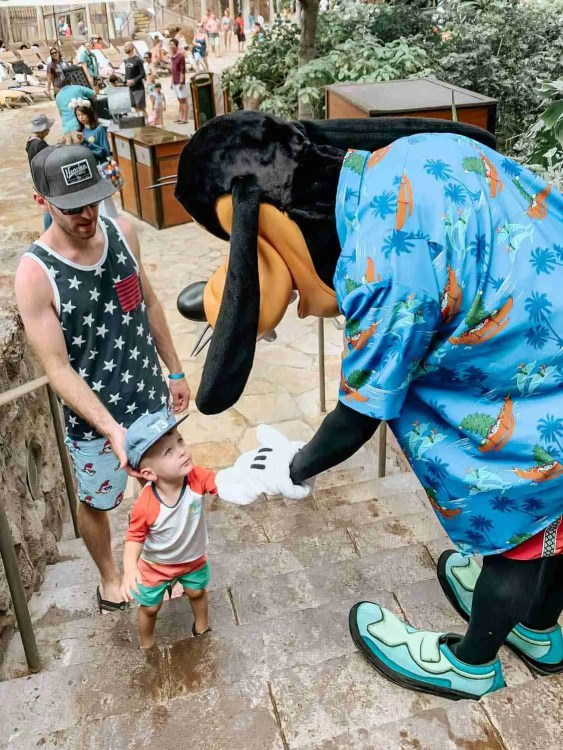 Little boy giving Disney character Goofy a high five while climbing stair at Aulani in Hawaii