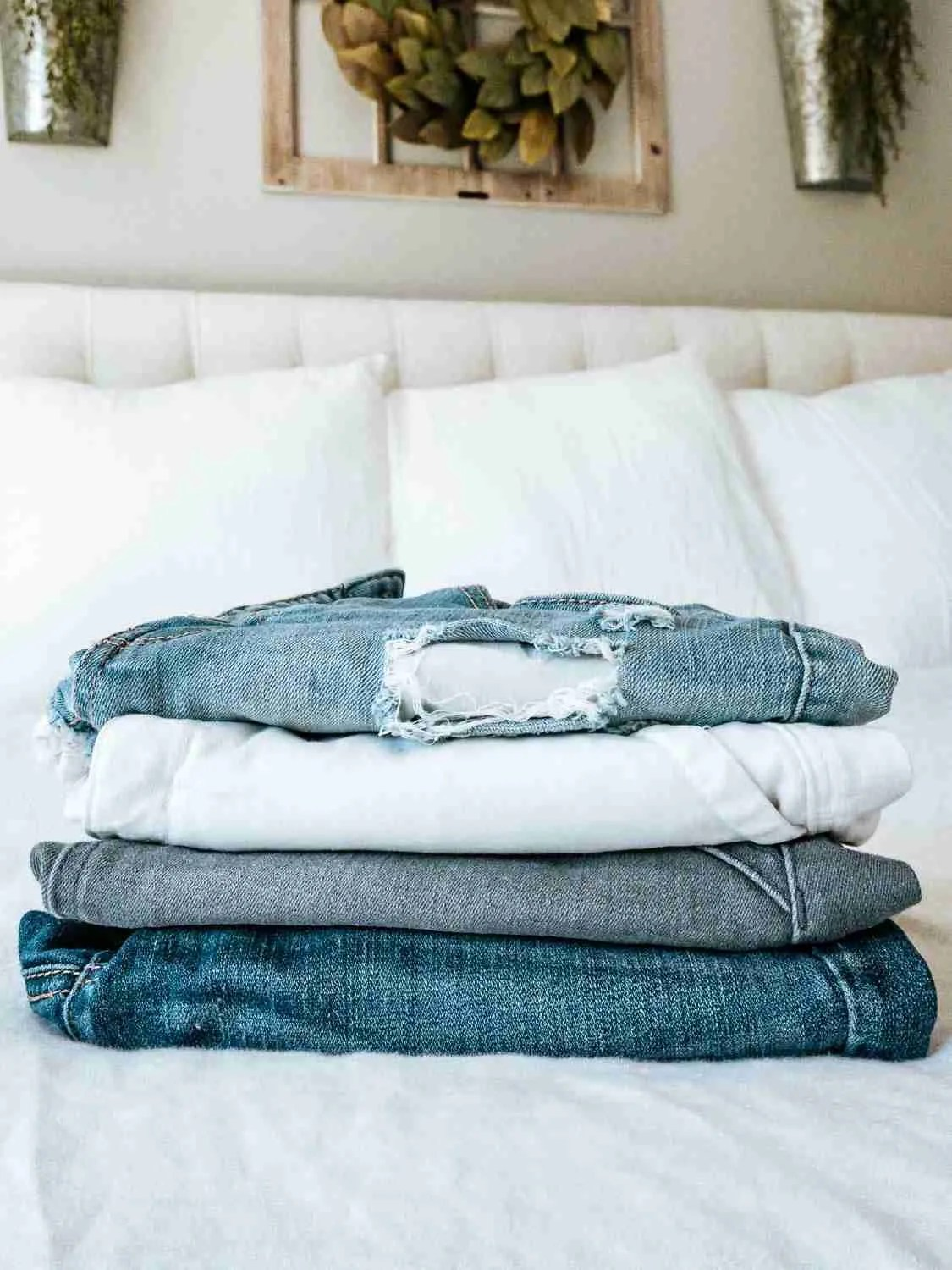 Jeans stacked on bed from a capsule wardrobe for minimalist travel