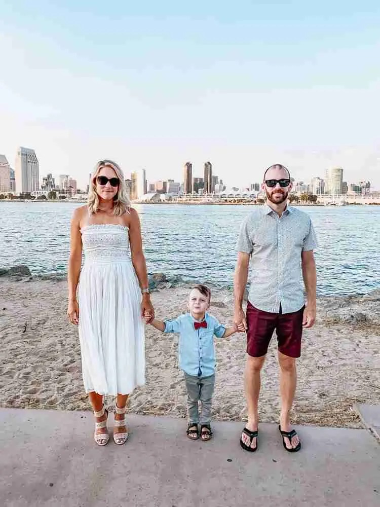 Family standing at shoreline of Coronado Island with San Diego bay and skyline behind them
