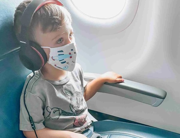 Little boy on airplane wearing masks with planes