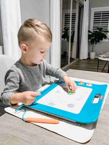 Toddler boy playing with magnetic drawing pad