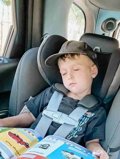 Toddler boy napping on a road trip