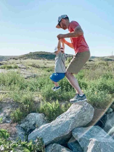 Father and son jumping off rocks