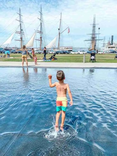 Little boy jumping in water at Waterfront Park by Star of India