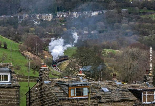 Seen from above the rooftops of Oakworth Road, 34092 'Wells' approaches Oakworth Station.