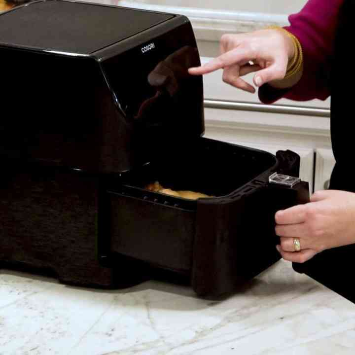 Image of a hand pulling out the air fryer basket of the Cosori Air Fryer