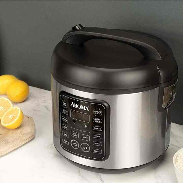 aroma rice cooker on a counter top with cut lemons sitting next to it