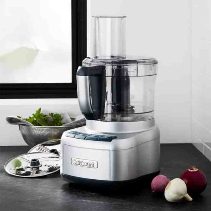 Image of a cuisinart food processor sitting on a kitchen counter with fresh produce surrounding it