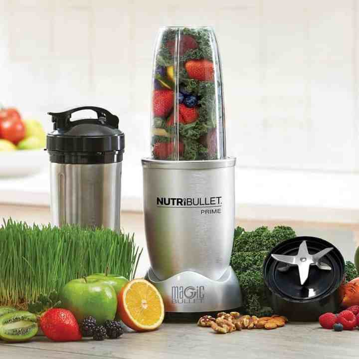 nutribullet personal blender on a counter with fruits and veggies