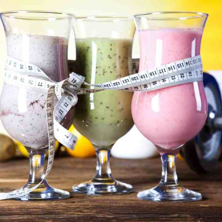3 bariatric protein powders turned into shakes served in glasses with a tape measure wrapped around it
