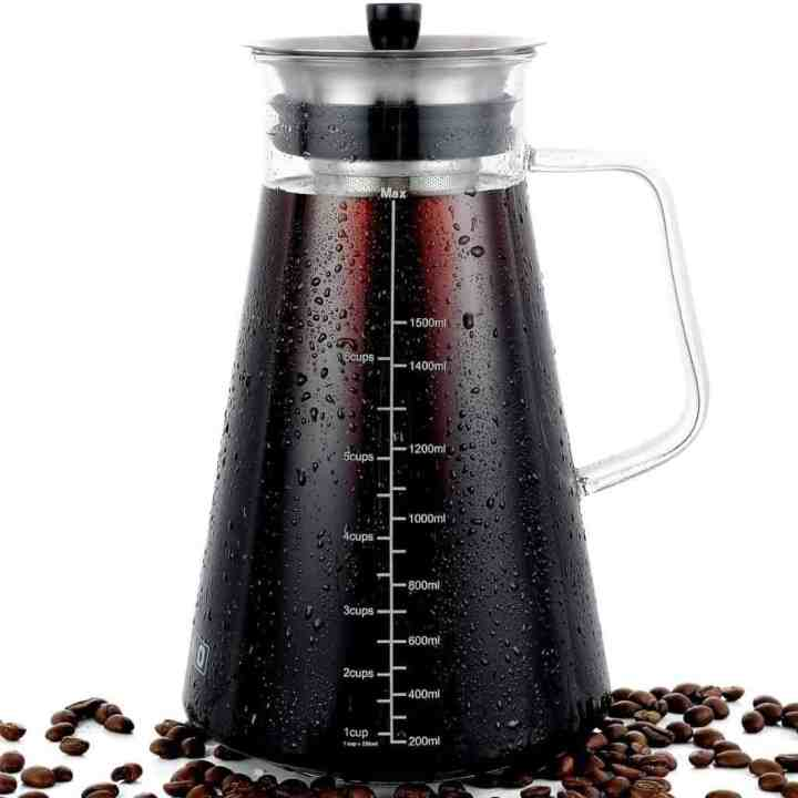 image of a cold brew coffee maker with coffee beans scattered around the base