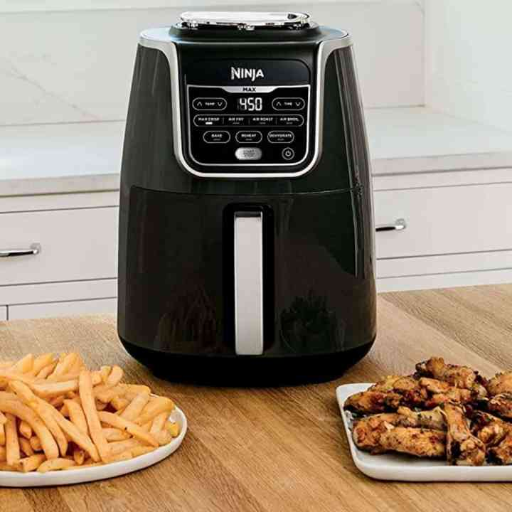 image of a ninja air fryer with plates of food sitting next to it