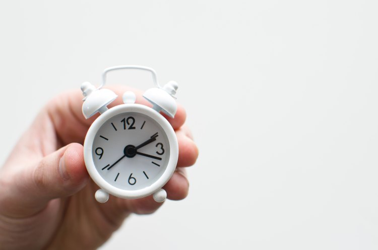 Small alarm clock in someone's hand