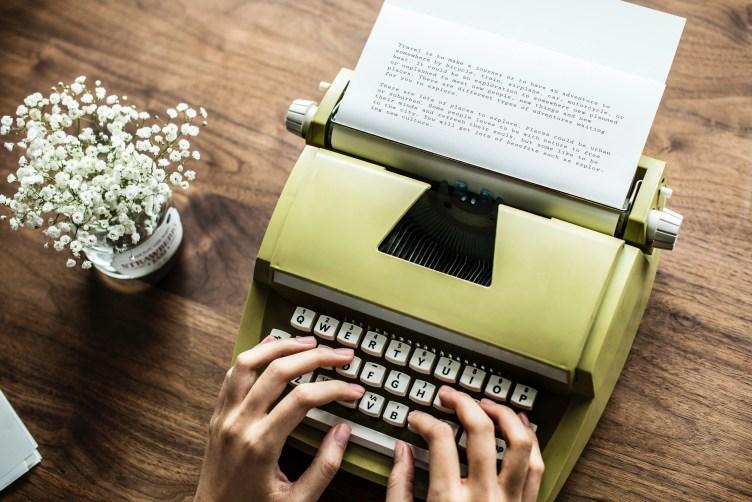Someone typing on a pale green typewriter