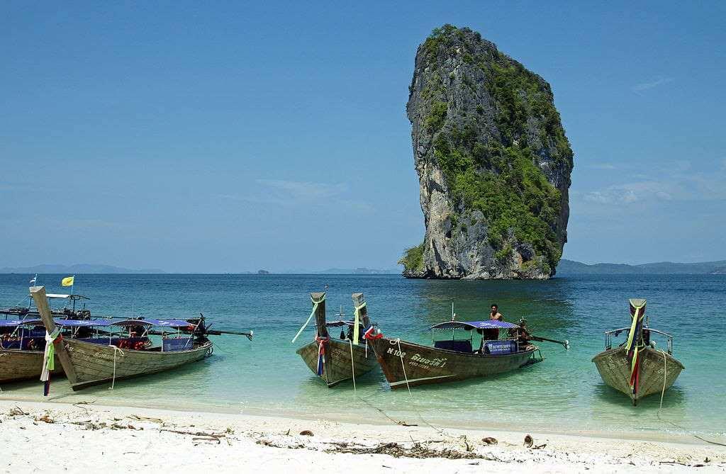 The beach of Poda island with long-tail boats, Krabi, Thailand -by kallerna/Wikimedia Commons