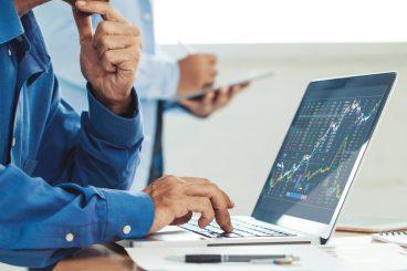 dua-pessoas-diante-de-computador-analisando-os-indices-de-liquidez