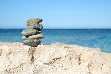 pedras-equilibradas-diante-do-mar-para-ilustrar-uma-vida-equilibrada