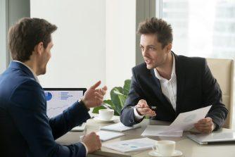homens-negociando-para-homem-diante-de-seu-computador-buscando-oportunidades-para-comprar-uma-empresa-em-funcionamento