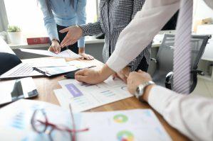 foto-de-gestores-analisando-graficos-e-tabelas-que-representam-a-dre