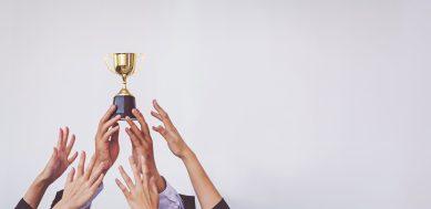 maos-segurando-um-trofeu-que-representa-a-vitoria-das-micro-e-pequenas-empresas-em-relacao-ao-refis