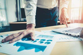foto-de-homem-diante-de-graficos-e-tabelas-em-sua-mesa-que-ilustram-o-planejamento-financeiro-empresarial
