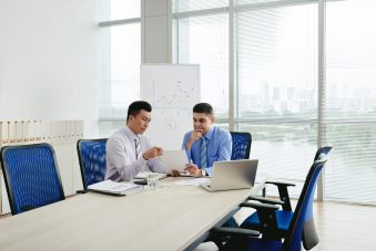 foto-de-dois-homens-em-uma-sala-de-reuniao-avaliando-contratos-com-a-clausula-mac
