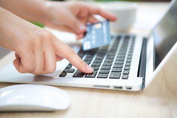 foto-de-pessoa-usando-o-computador-com-seu-cartao-de-credito-em-maos-optando-pela-melhor-linha-de-credito