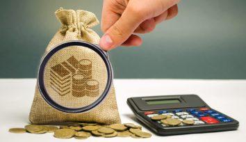 lupa-diante-de-saco-de-dinheiro-com-calculadora-ao-lado-para-analisar-e-reduzir-gastos
