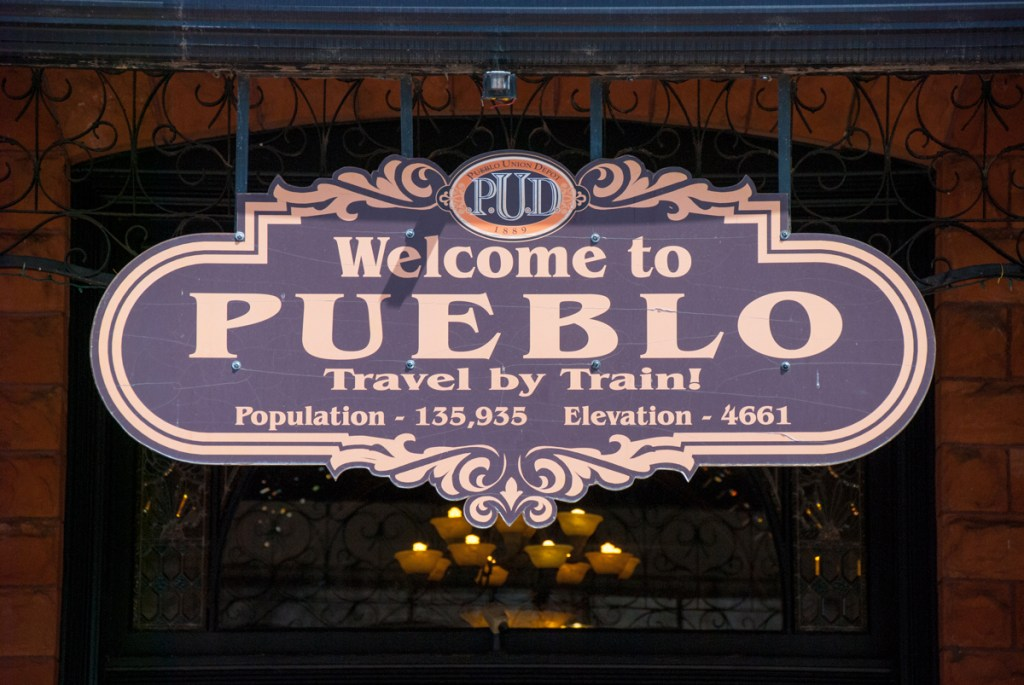 A sign at Pueblo's Union Depot advertises travel by rail