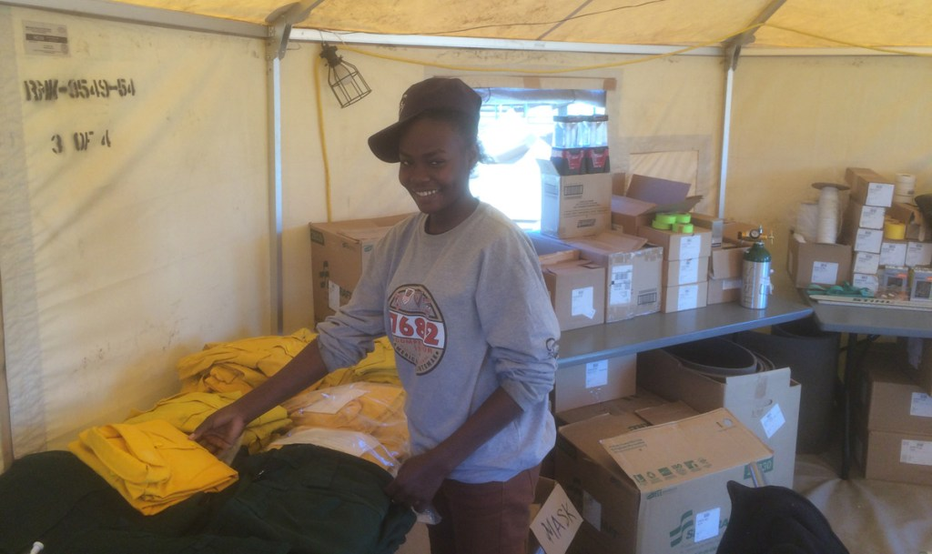 Nasim Abakar, a 19-year-old student originally from Sudan, works in the supply tent at the Hayden Pass Fire base camp.