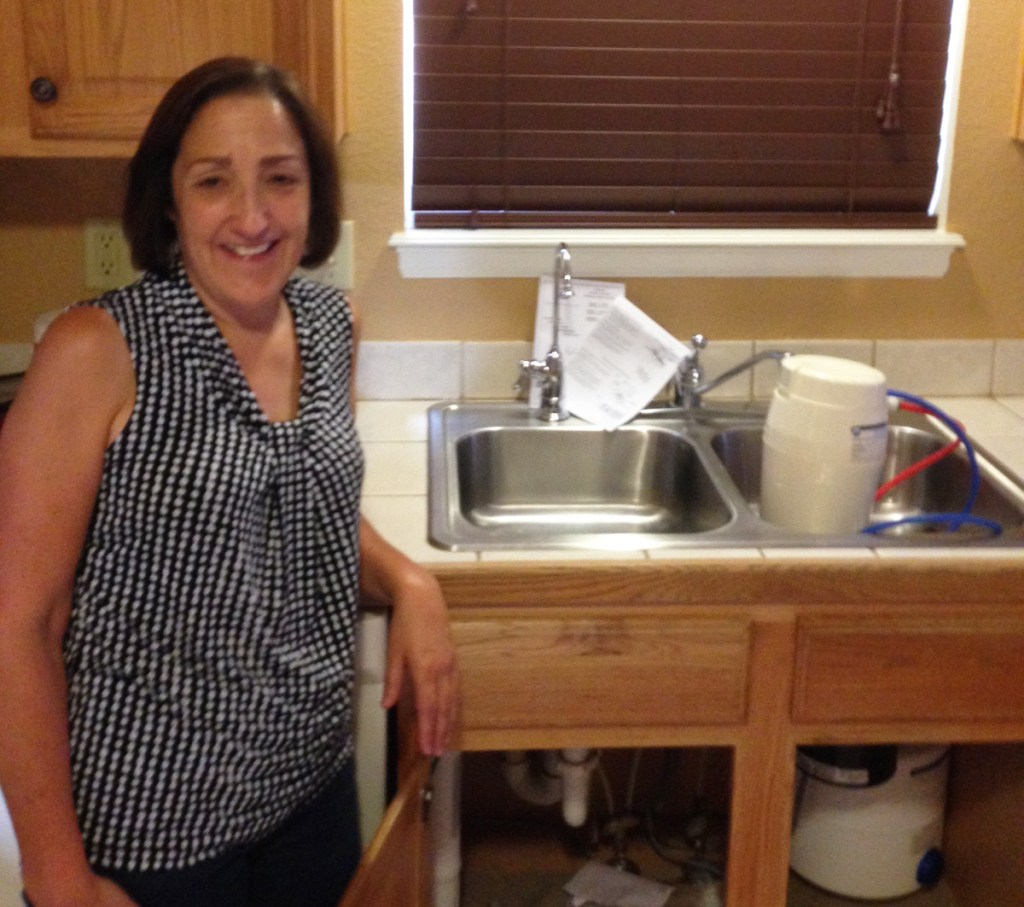Debbie Maiurro stands beside the sink at her home in Widefield. She and her sister, who she lives with, chose to install a reverse osmosis water filter under the sink after learning about PFC contamination in the local water supply.