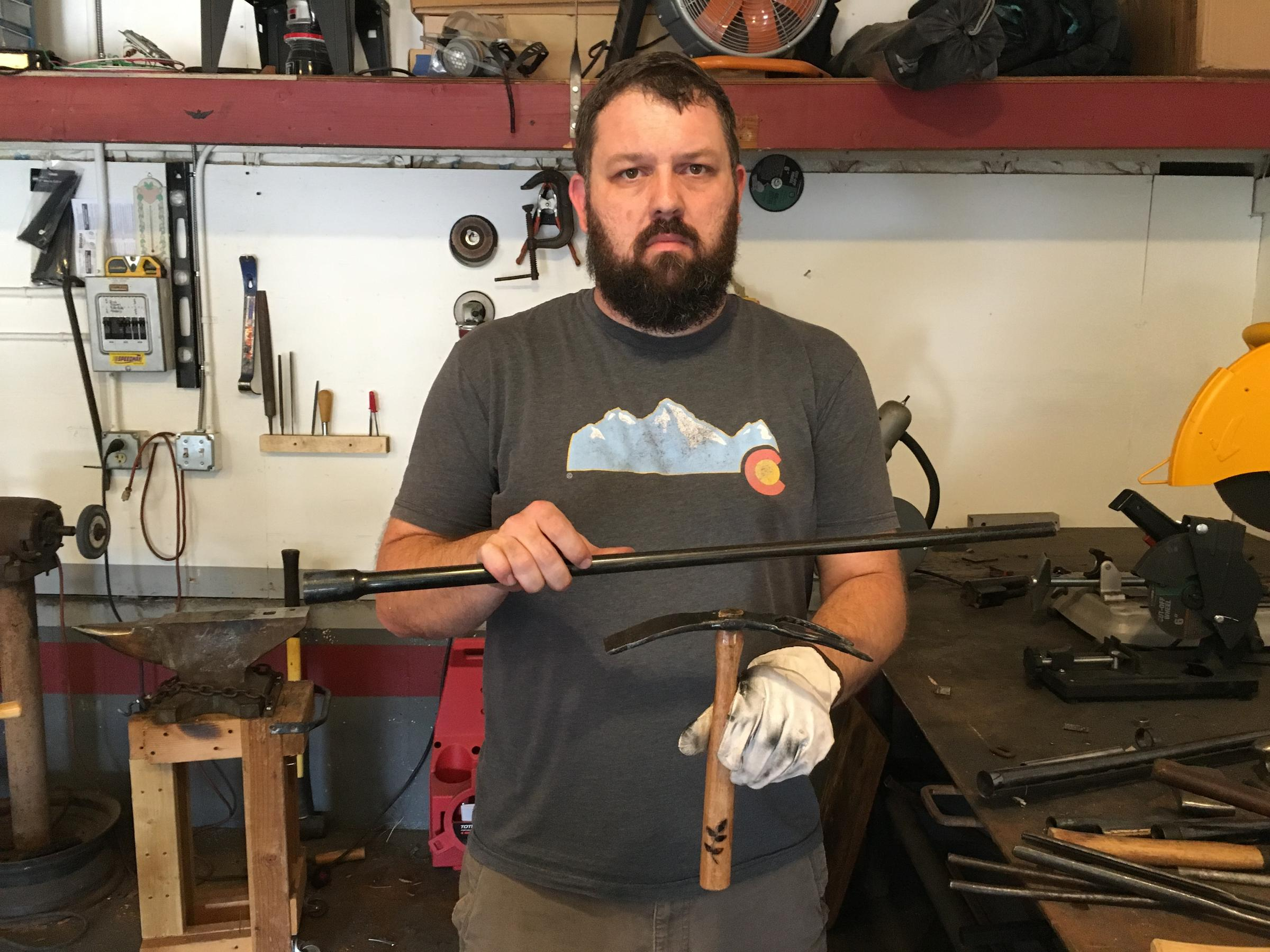 Mike Martin, founder of RAWtools, holds a garden tool and a rifle barrel like the one from which it was made.