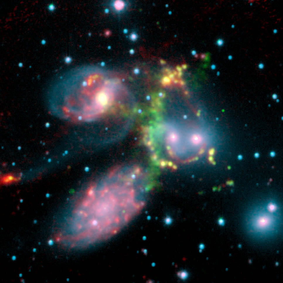 This false-color composite image of the Stephan's Quintet galaxy cluster clearly shows one of the largest shock waves ever seen (green arc). The wave was produced by one galaxy falling toward another at speeds of more than one million miles per hour. The image is made up of data from NASA's Spitzer Space Telescope and a ground-based telescope in Spain.