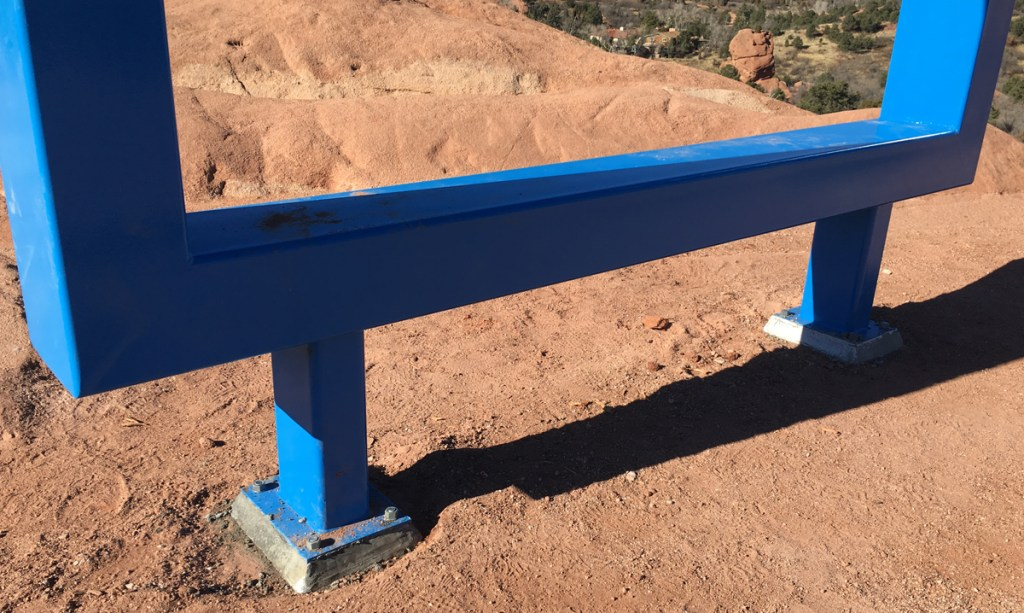 The blue frame affixed to the ground in Garden of the Gods park, at the edge of the High Point Overlook parking lot.