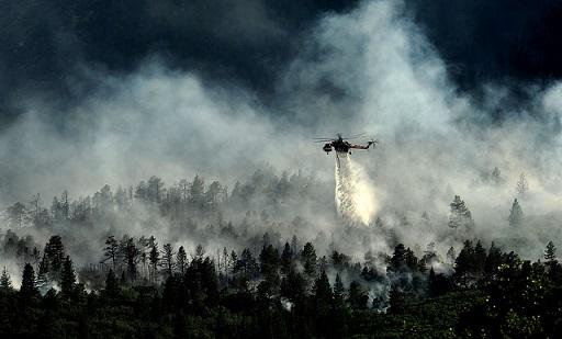 A helicopter drops water on a wildfire as firefighters continue to battle the blaze in Waldo Canyon, Colo., in 2012.