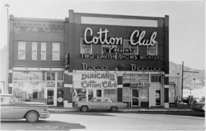 "Exterior of the Cotton Club with cars in front. Signs on building include ""Cotton Club Presents Two Lavish Shows Nightly. Dining - Dancing. Duncan's Cotton Club."" Sign in window reads ""Barber Shop Yes We're Open."""