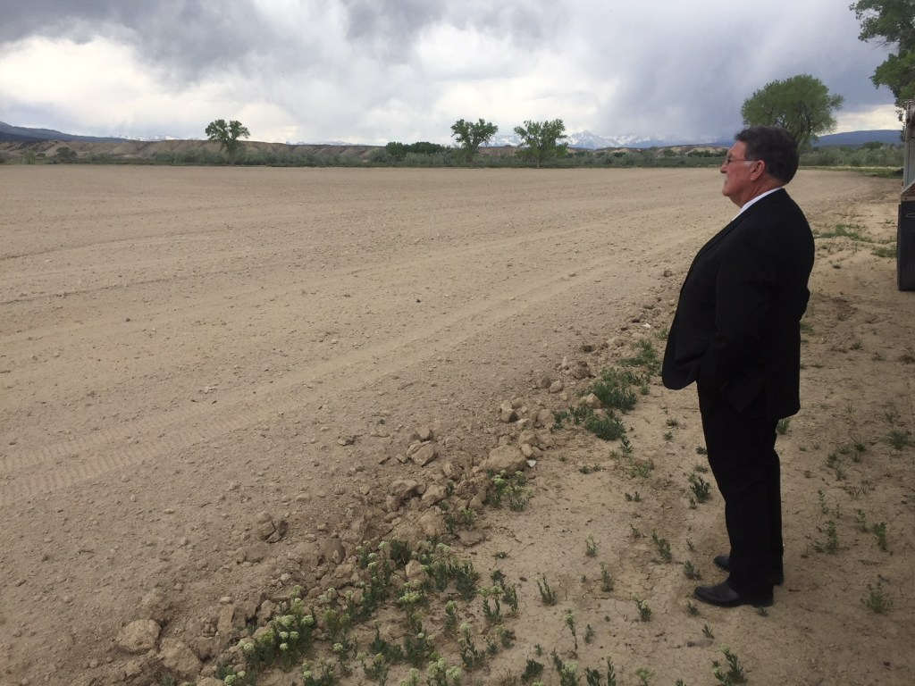 Senator Don Coram next to field ready for hemp planting