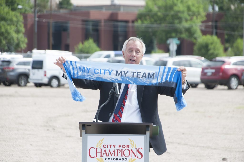 Colorado Springs Switchbacks owner Ed Ragain holding a Switchbacks team scarf as he discusses the new stadium at a press conference Wednesday.