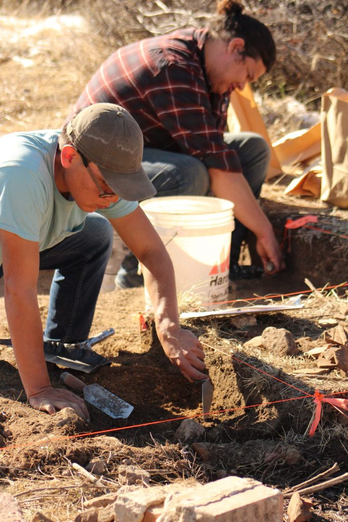 Archaeologists dig through layers of dirt at the site.