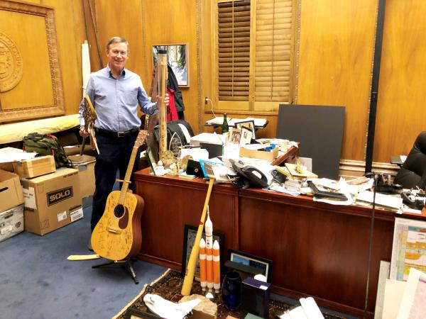 Gov. John Hickenlooper poses at his desk during one of his final days in office. The office was more cluttered than usual as the governor packed up several pieces of memoribilia.