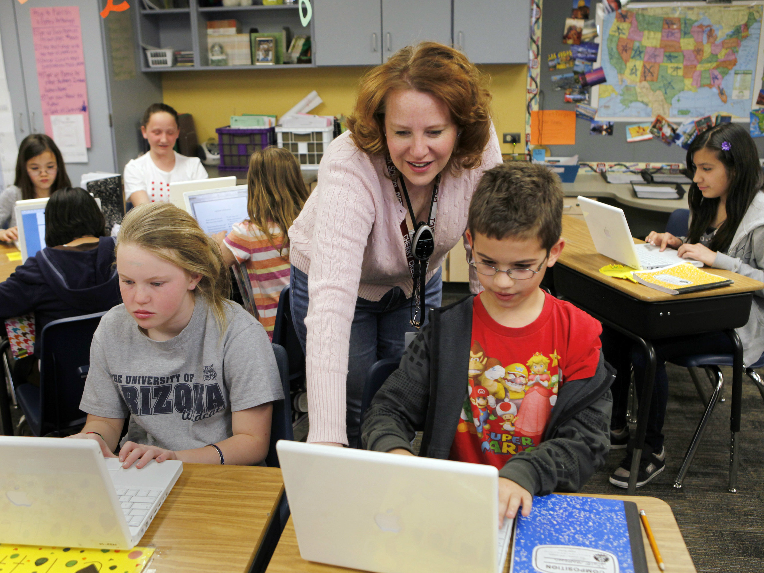 <p>In this April 22, 2011 photo, High Plains Elementary School teacher Jennifer Williford, center, works with Colette Jackson, 11, and Skyler Matteson, 10, right, on a computer project in her fifth grade class at the school in Englewood, Colo.</p>