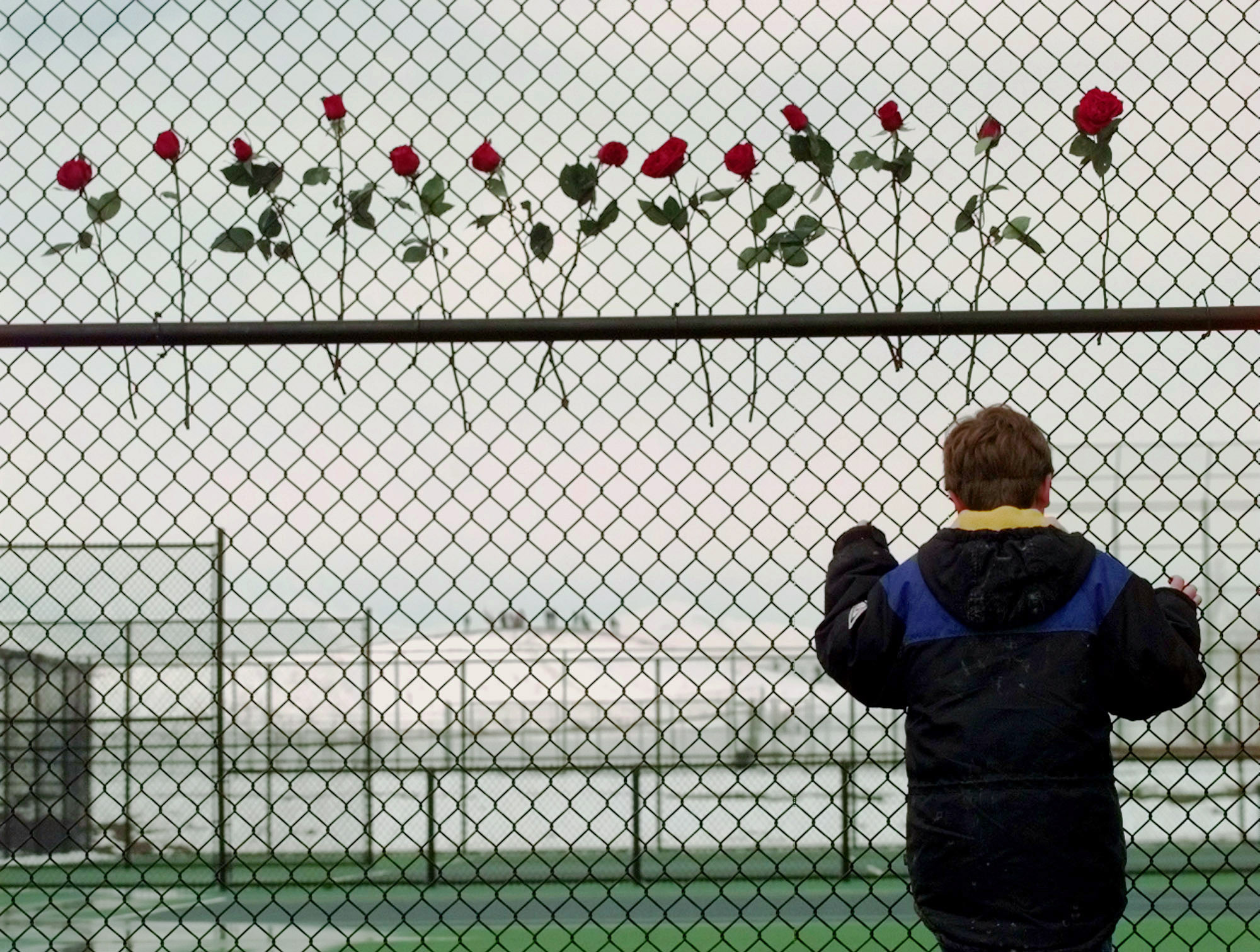 <p>A boy looks through the fence at the Columbine High School tennis courts in Littleton, Colo., days after theApril 20, 1999 shootings.</p>